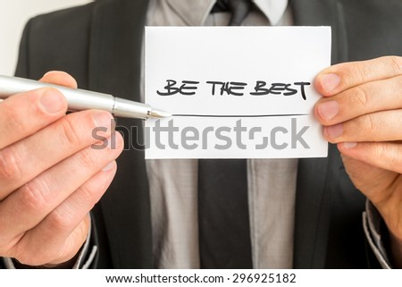 Closeup of personal therapist showing a white card with a Be the best sign encouraging you to live up to your fullest potential and realise your goals and dreams. - stock photo