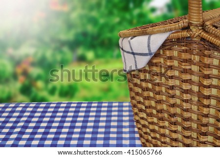 Closeup Of Picnic Basket On The Table With Blue Checkered Tablecloth And Summer Garden In The Background - stock photo