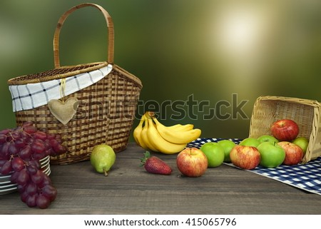 Closeup Of Picnic Basket With Fruits On The Table With Blue Checkered Tablecloth And Summer Garden In The Background - stock photo