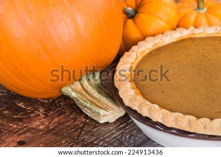 Closeup of pie pumpkin and a homemade pumpkin pie, wooden background  - stock photo
