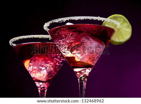 Closeup of pink cocktails in martini glasses with sugared edges, ice cubes and lime slices - stock photo
