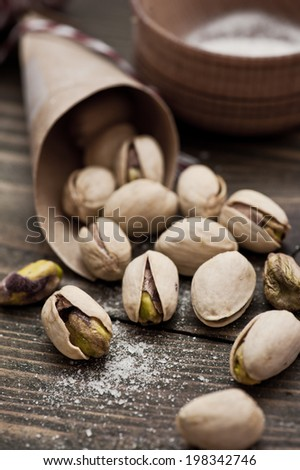 Closeup of pistachios nuts and salt on dark brown wooden table. Sepia toned image - stock photo