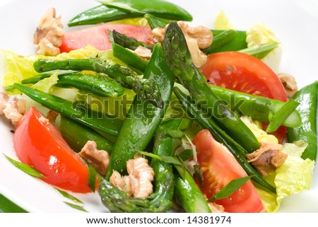 Closeup of plate of asparagus, snow pea and tomato salad with ginger dressing.