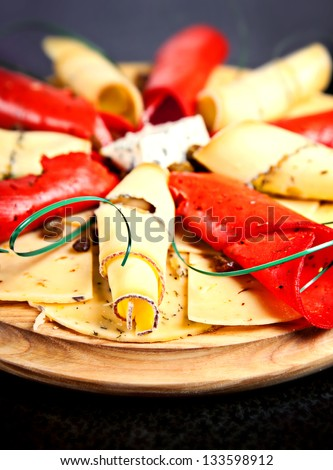 Closeup of plate with different slices of cheese on black background - stock photo