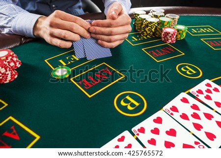 Closeup of poker player with playing cards and chips  - stock photo