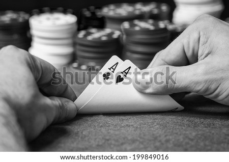 Closeup of poker player with two aces in black and white - stock photo