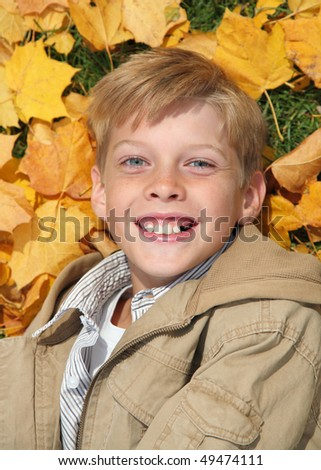 closeup of preadolescent male lying on leaves in fall - stock photo