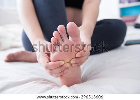 Closeup of pregnant woman hands doing foot massage  - stock photo