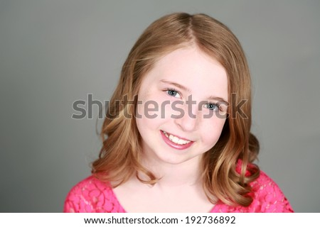closeup of preteen girl smiling and looking at camera - stock photo