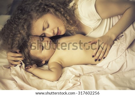 Closeup of pretty tender young loving mother with light blonde curly hair touching little tiny cute male lovely baby indoor in bed with white linen lying close to each other, horizontal picture - stock photo