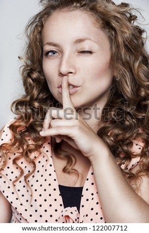 Closeup of pretty woman making silent gesture