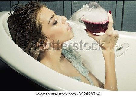 Closeup of pretty young sensual woman with wet hair sitting in white bath tab holding in hand drinking glass with red liquid with smoke as elixir of beauty indoor, horizontal picture - stock photo