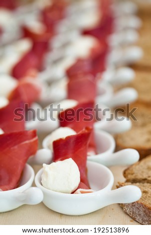 Closeup of prosciutto ham and ball shaped mozzarella cheese appetizers in rows of small white serving dishes and row of bread slices - stock photo