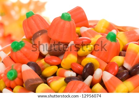 Closeup of pumpkin filled with delicious Halloween candy over fall leaves background - stock photo