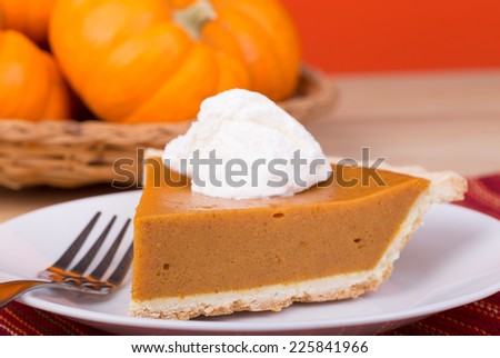 Closeup of pumpkin pie slice with pumpkins in background - stock photo