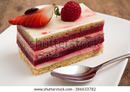 closeup of raspberry cake in a plate on wooden table