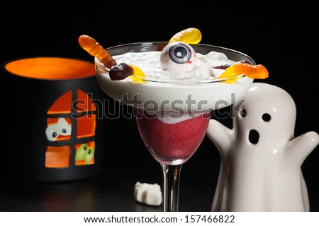 Closeup of Raspberry Vanilla Daiquiri cocktail, garnished with Gummy Worms and candy. Rum, raspberry, liqueur, and lime juice over black background. Halloween drinks series  - stock photo