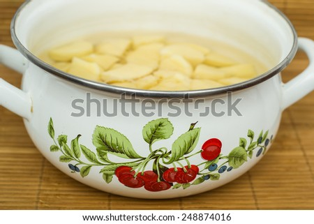 Closeup of raw peeled potatoes in pot isolated on bamboo mat - stock photo