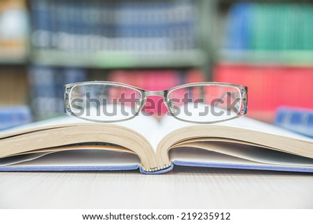 Closeup of reading glasses on the book - stock photo