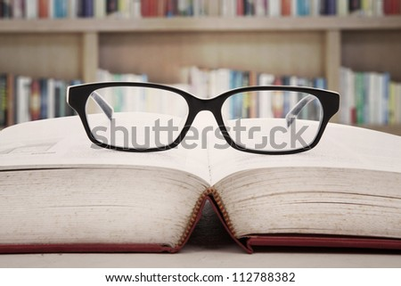 Closeup of reading glasses on the book. shot in the library - stock photo