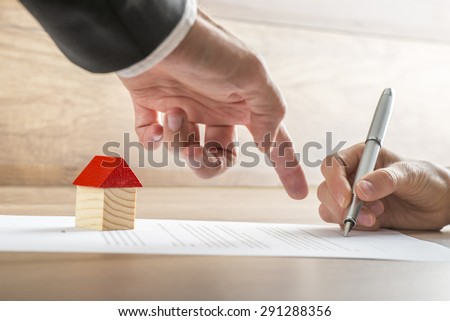 Closeup of real estate agent showing his client where to sign a contract of house sale or mortgage papers. Suitable for real estate concept.  - stock photo