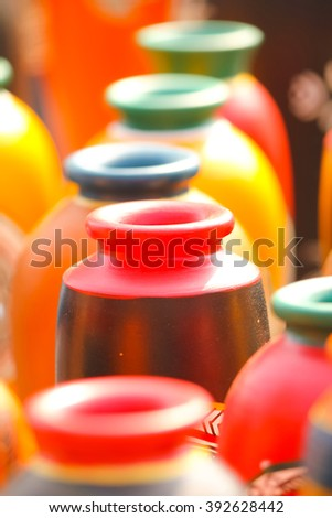 Closeup of red-brown colored earthen vase in a row; selective focus