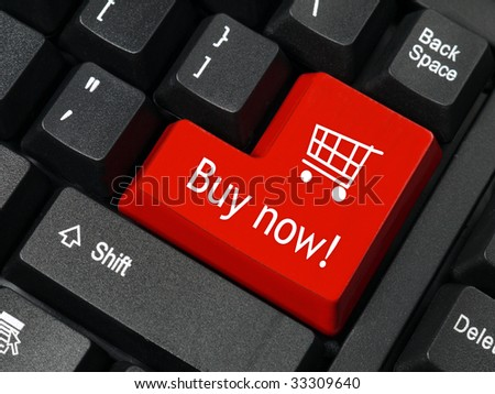 Closeup of red computer keyboard key with shopping cart symbol and Buy Now text
