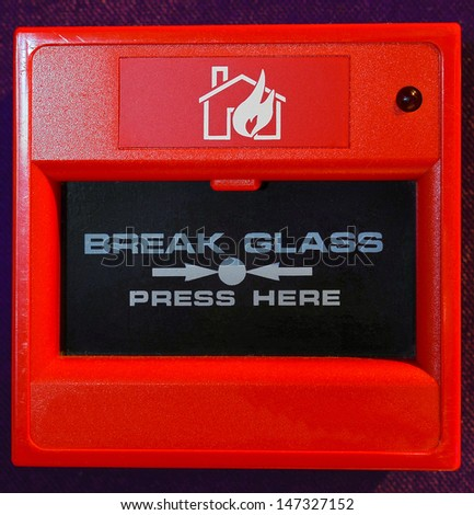 Closeup of red fire alarm button. - stock photo