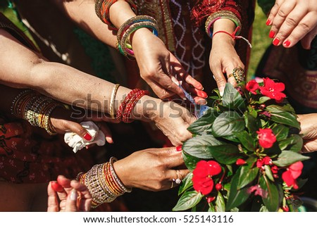 Closeup of red flowers held by Indian women