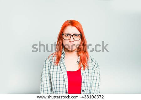 closeup of red-haired girl angry, wears glasses - stock photo