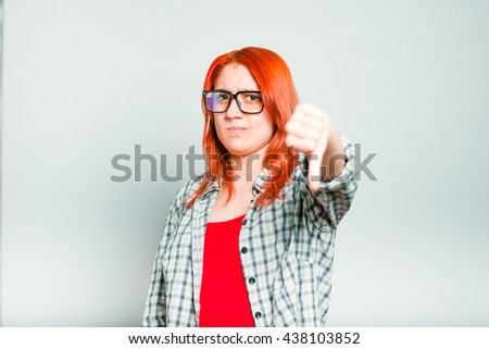 closeup of red-haired girl shows her dislike, thumbs down, wears glasses