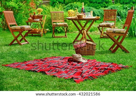 Closeup Of Red Picnic Blanket With Cowboy Straw Hat And Basket Or Hamper. Blurred Outdoor Wooden Furniture In The Background. Family Home Backyard Party Or Picnic Conceptual Scene - stock photo