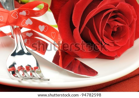 Closeup of red rose and cutlery on white plate - stock photo