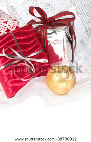 Closeup of red, silver, and gold wrapped Christmas gifts with pretty ribbons and ornaments. Silver star translucent fabric backdrop on white. Vertical format with copy space. - stock photo