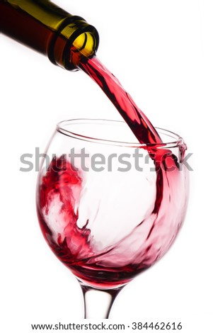 Closeup of red wine pouring into glass - stock photo