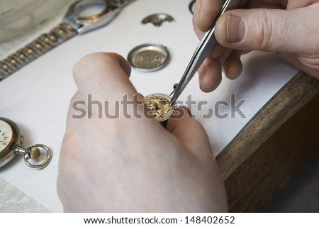 Closeup of repairman's hands working on watch in workshop - stock photo