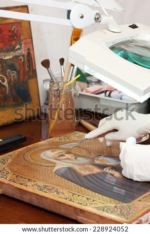 Closeup of restoration of ancient icon with  filling knife at restoration workshop - stock photo