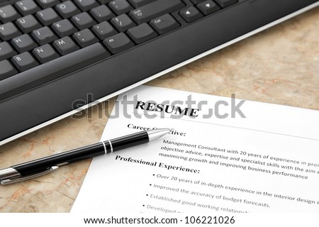 Closeup of Resume with Pen and Keyboard on the Table - stock photo