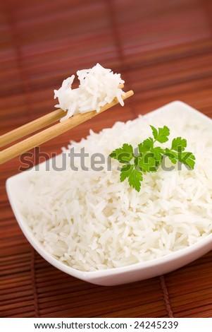 Closeup of rice on chopsticks and a bowl on mat - stock photo