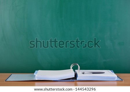 Closeup of ring binder and pen on desk against blank chalkboard - stock photo
