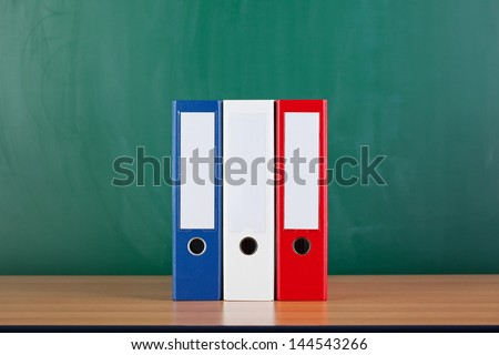 Closeup of ring binders on desk against blank chalkboard - stock photo