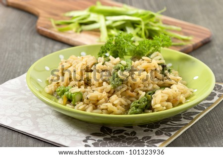 closeup of risotto with green asparagus on wooden background