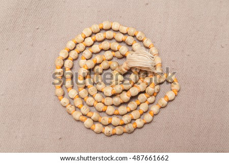 Closeup of rolled chanting beads on woolen texture