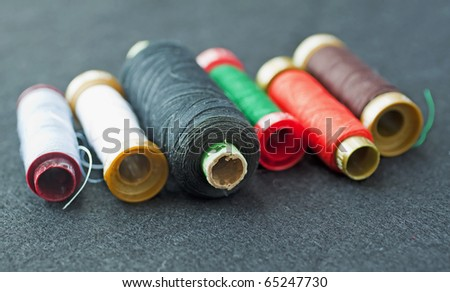 Closeup of rolls of sewing thread (focus on the black roll)
