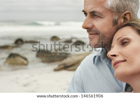 Closeup of romantic couple looking away at beach - stock photo