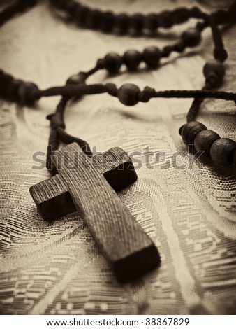 closeup of rosary cross,shallow DOF with focus on the cross, light sepia toned with vignette - stock photo