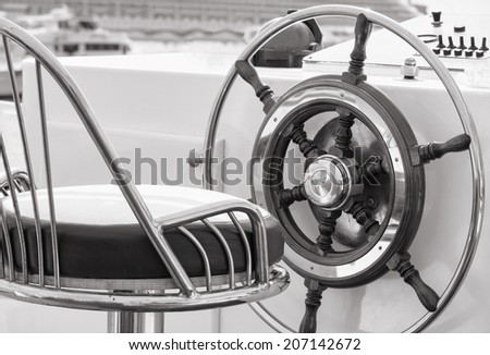 Closeup of rudder and chair in a luxury boat in black and white.