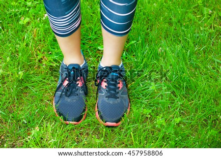 Closeup of running shoes on grass - concept image.