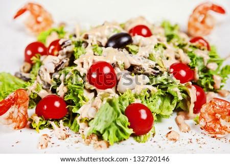 Closeup of salad with shrimp, tomatos and white sauce - stock photo