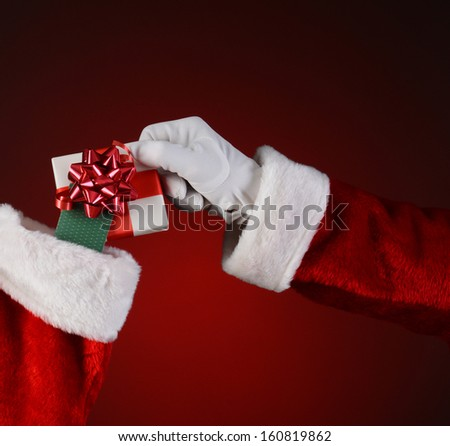 Closeup of Santa Claus placing a small wrapped present into a holiday stocking.  Square format on a light to dark red spot background. - stock photo
